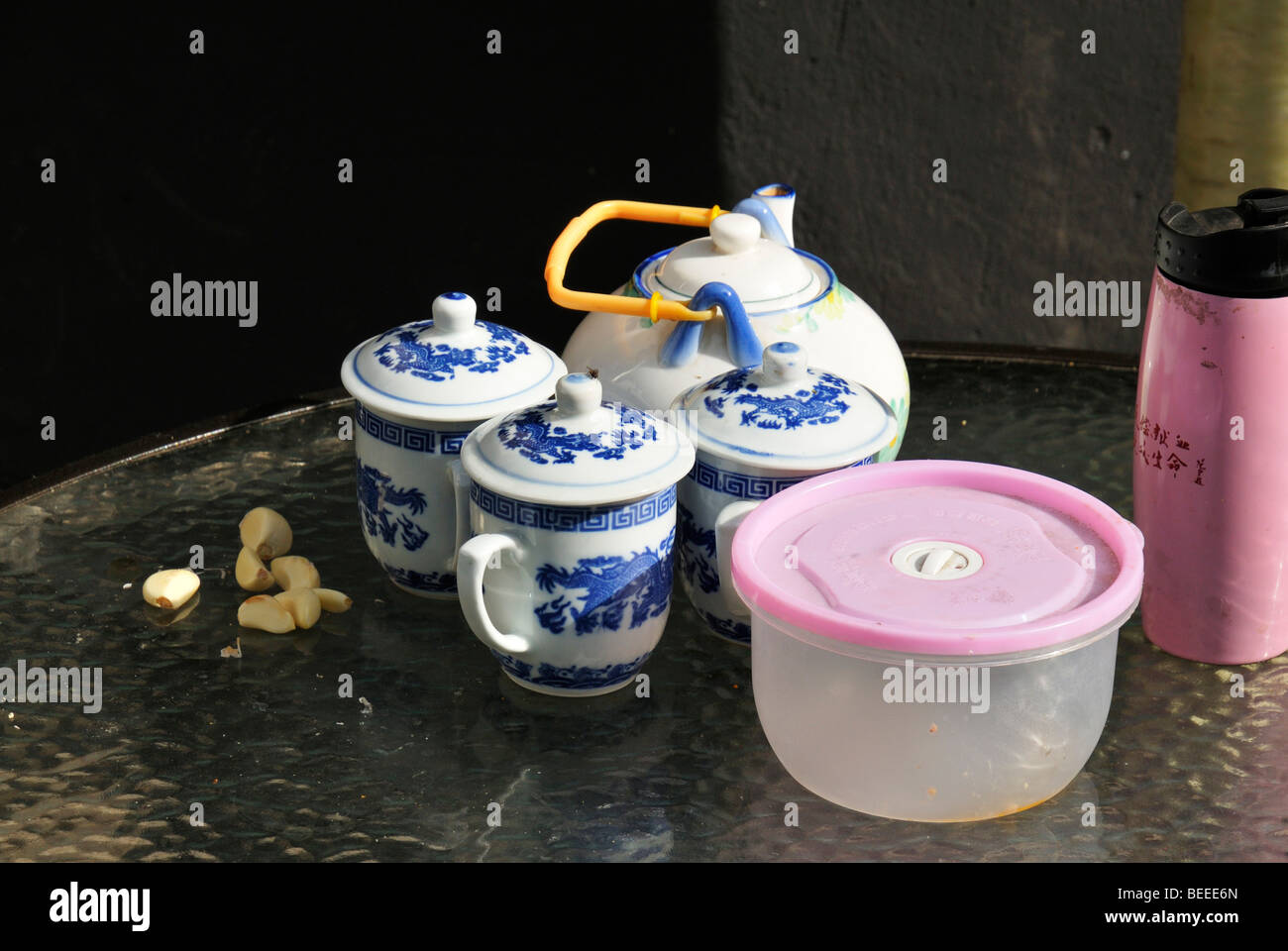 Cloves of garlic, a Chinese tea set and a pink thermos flask, Beijing, China - Stock Image