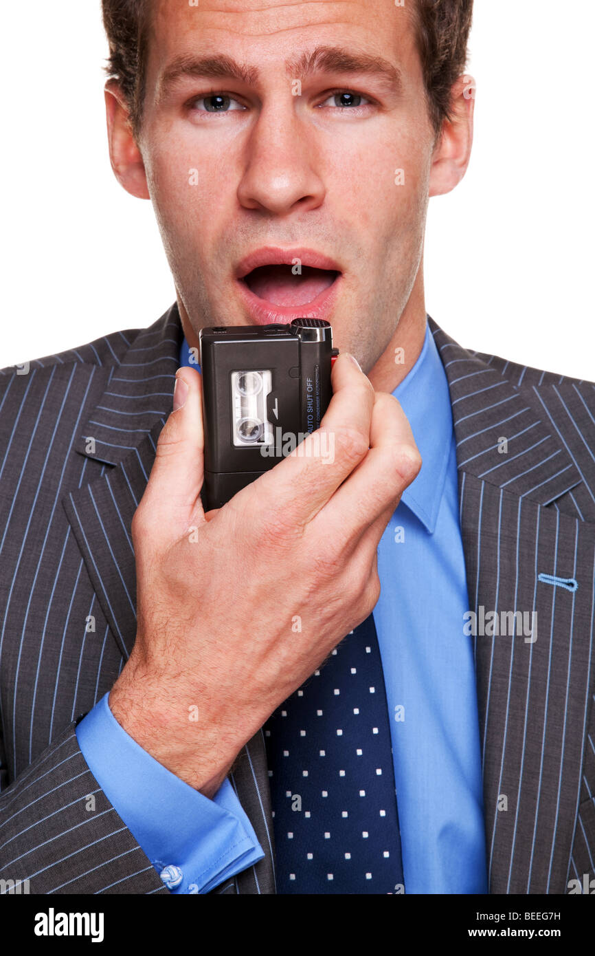 Businessman speaking into a dictation recorder - Stock Image