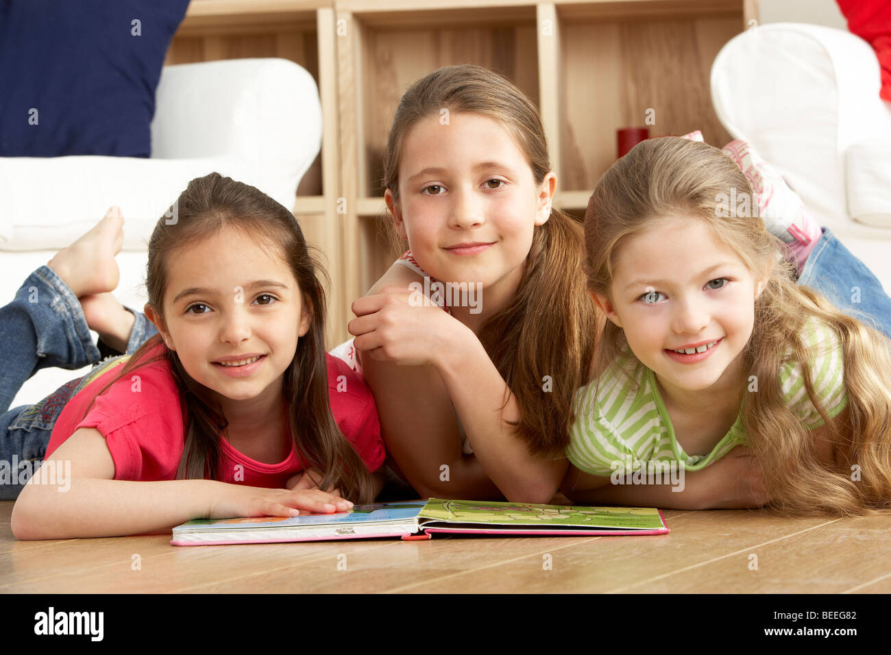 Three Young Girls Reading Book at Home - Stock Image