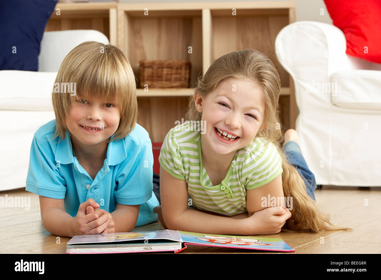 Two Young Children Reading Book at Home - Stock Image