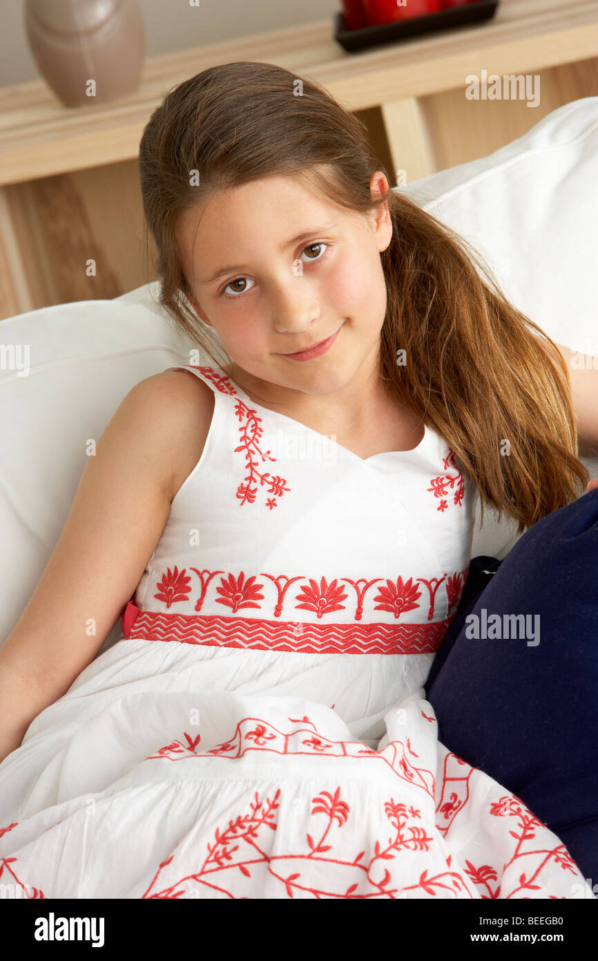Young Girl Sat on Sofa at Home - Stock Image
