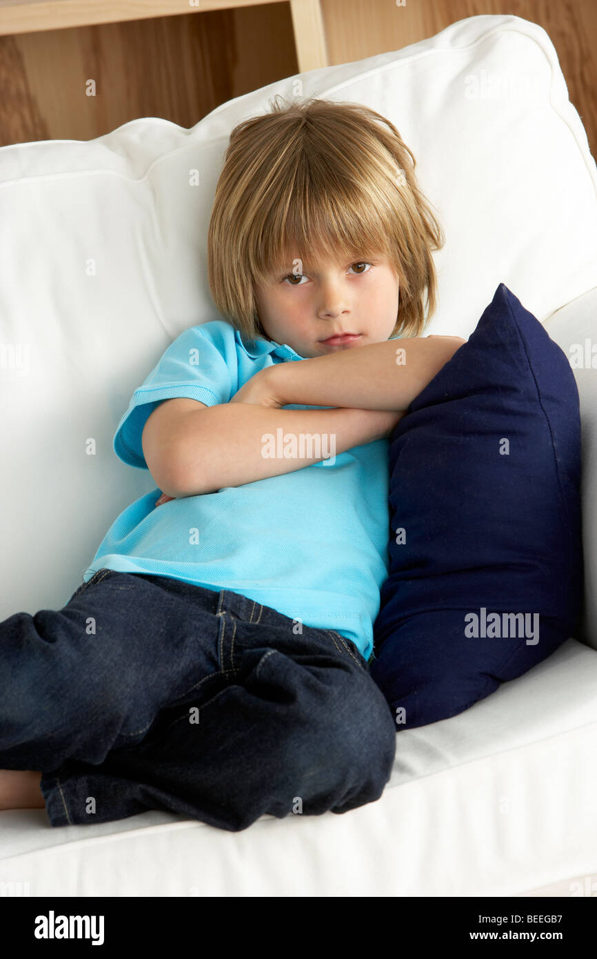 Young Boy Sat on Sofa at Home - Stock Image