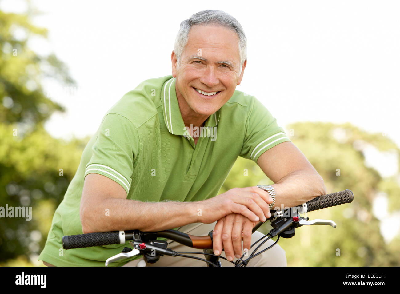 Portrait of man riding cycle in countryside - Stock Image