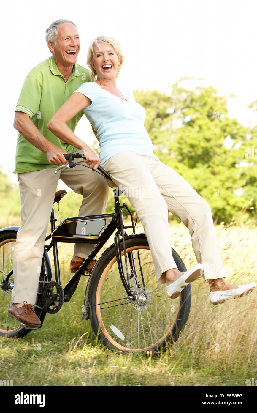 Mature couple riding bike in countryside - Stock Image
