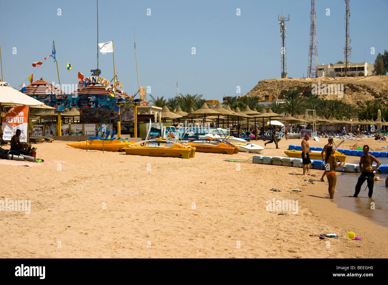 Tourists enjoying the sun at Naama Bay beach, Sharm el Sheikh, Red Sea, Egypt - Stock Image