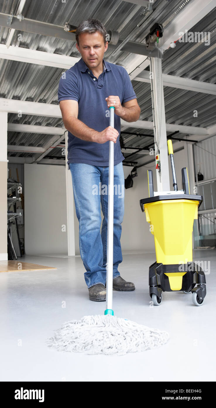 Cleaner mopping office floor - Stock Image