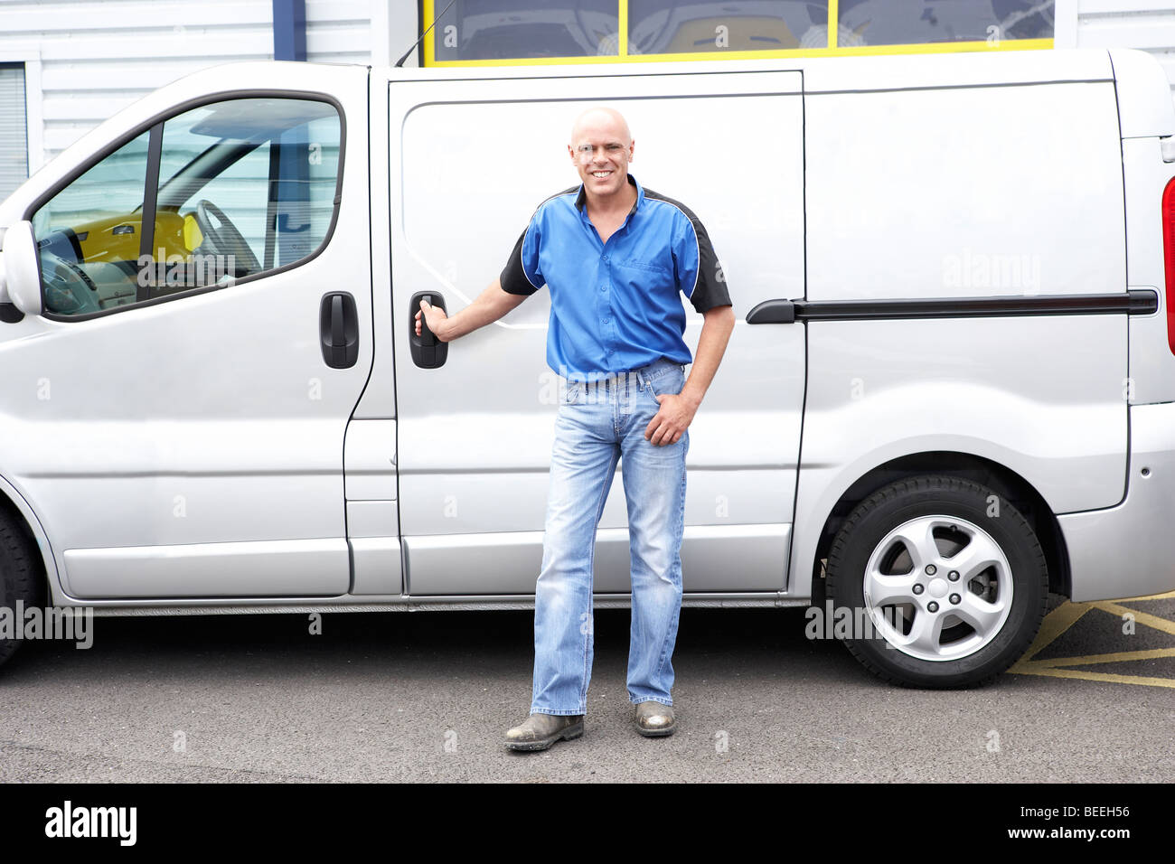 Man standing next to van - Stock Image
