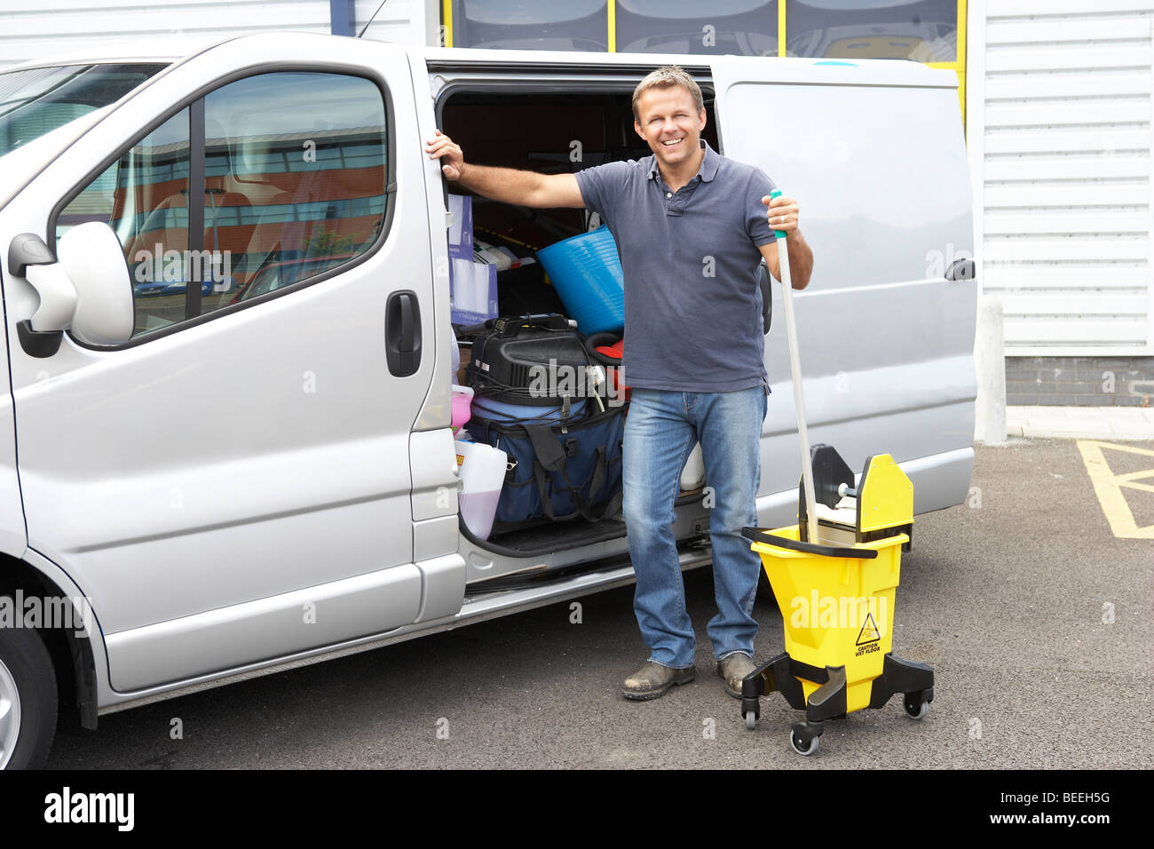 Cleaner standing next to van - Stock Image