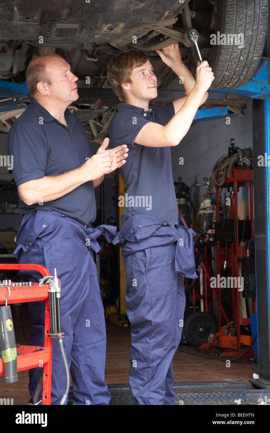 Mechanic and apprentice working on car - Stock Image