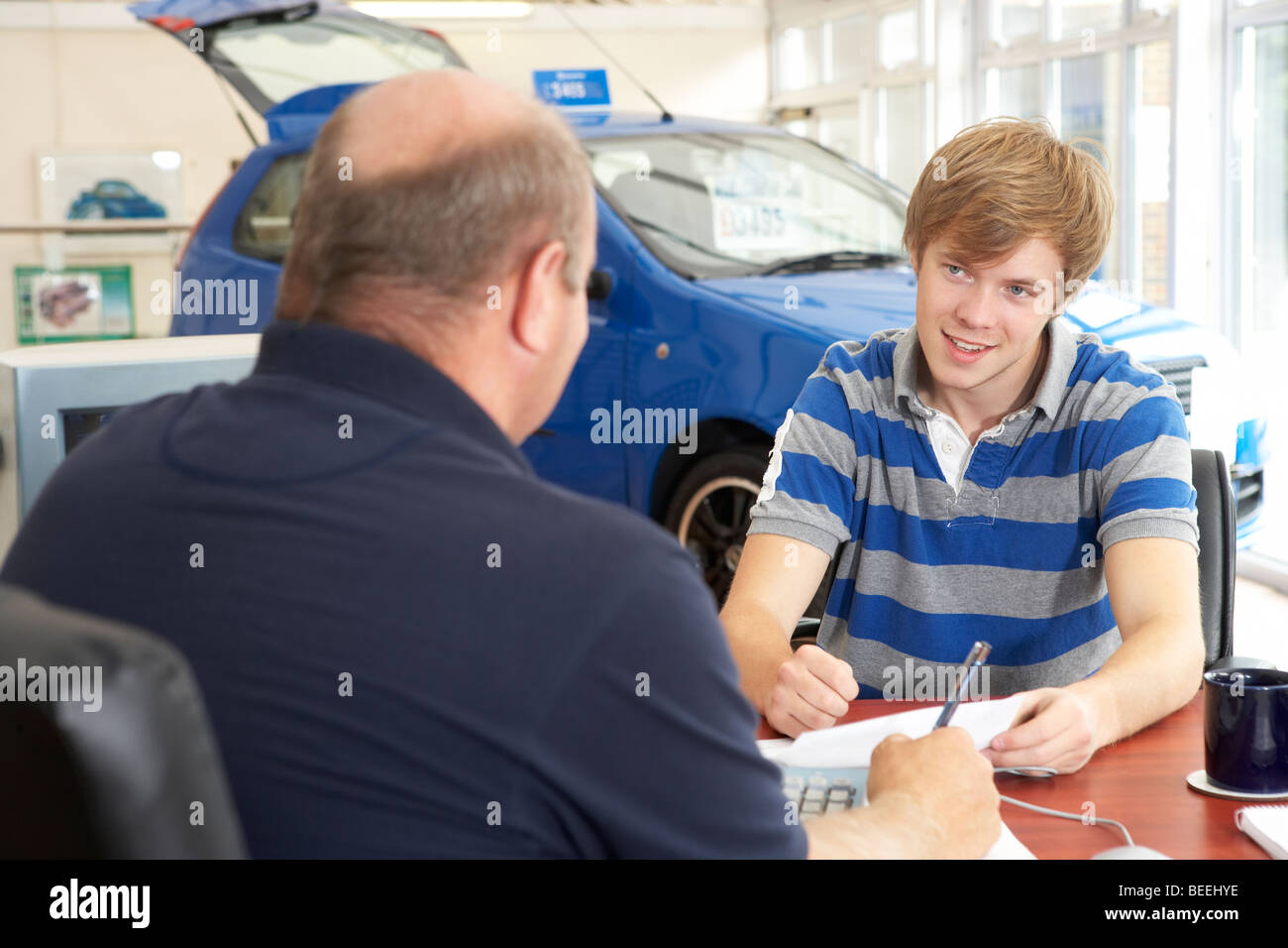 Young man filling in paperwork in car showroom - Stock Image