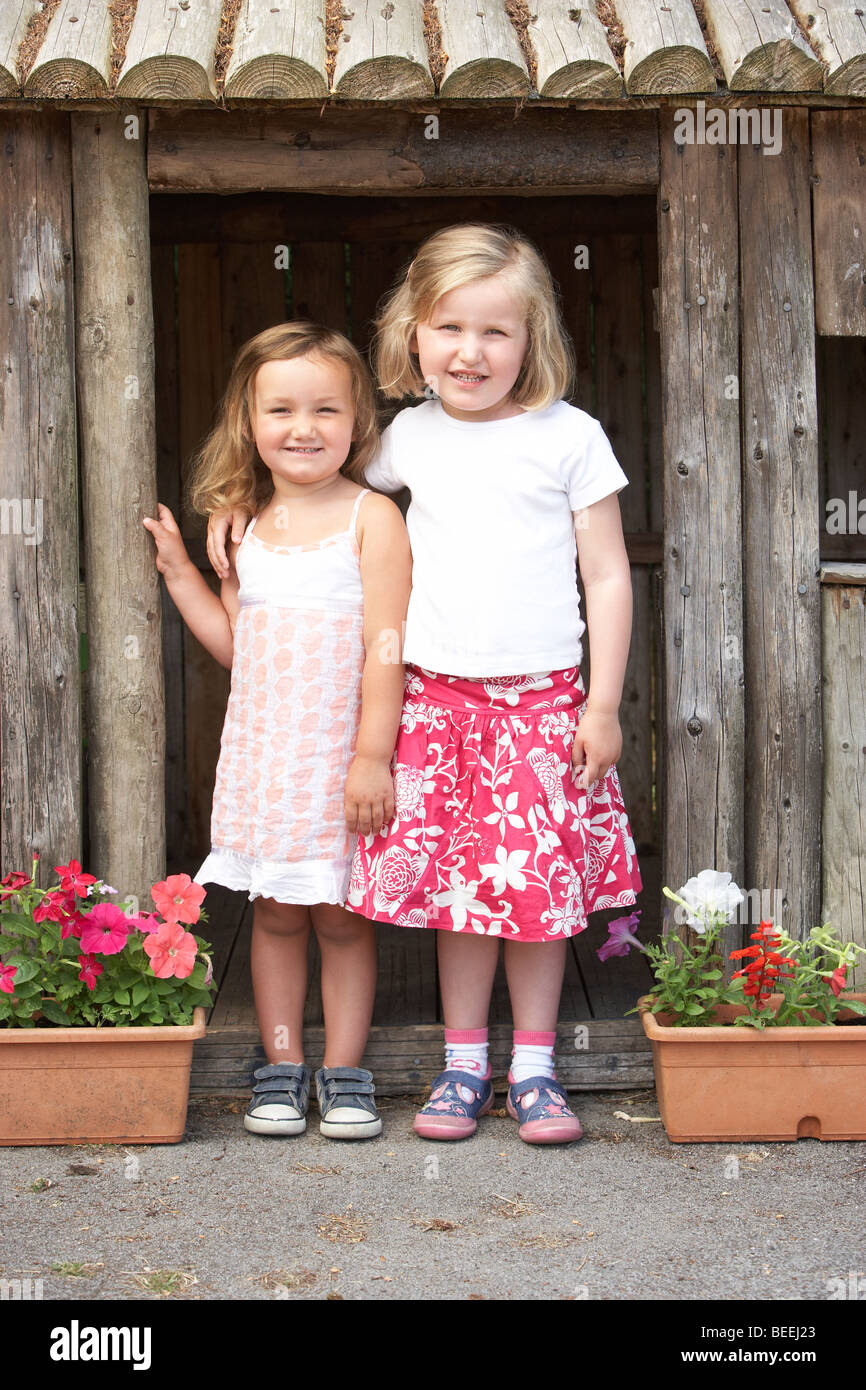 Two Young Girls Playing in Wooden House Stock Photo