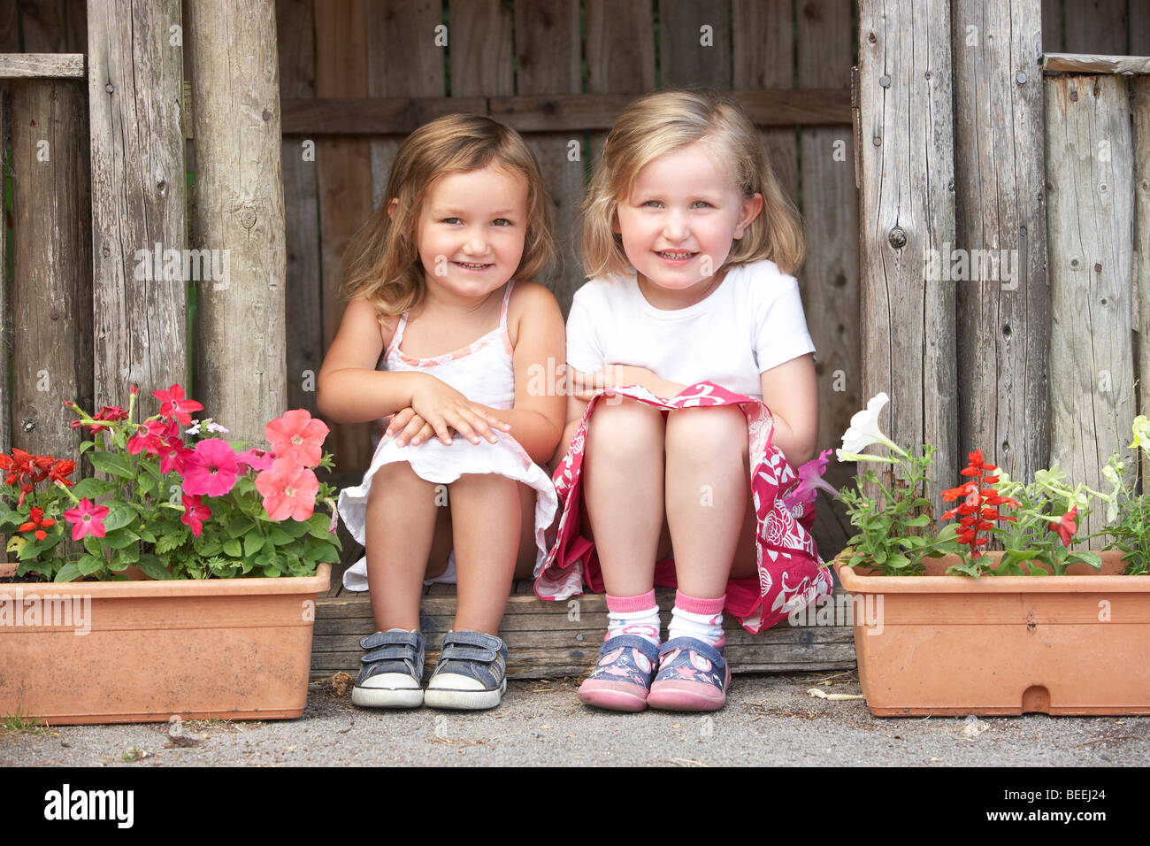 Two Young Girls Playing in Wooden House - Stock Image