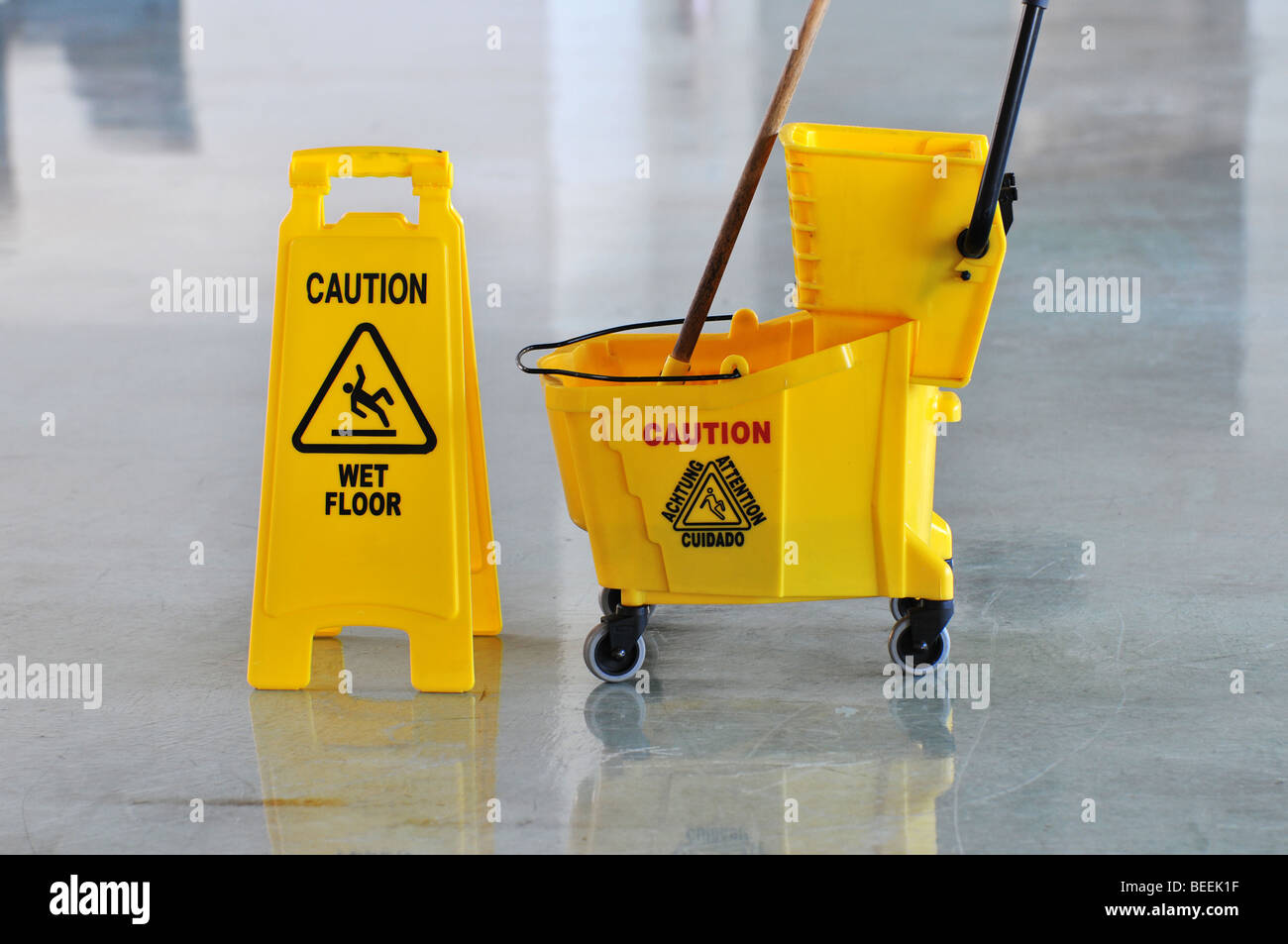 Mop bucket and caution sign on wet floor - Stock Image