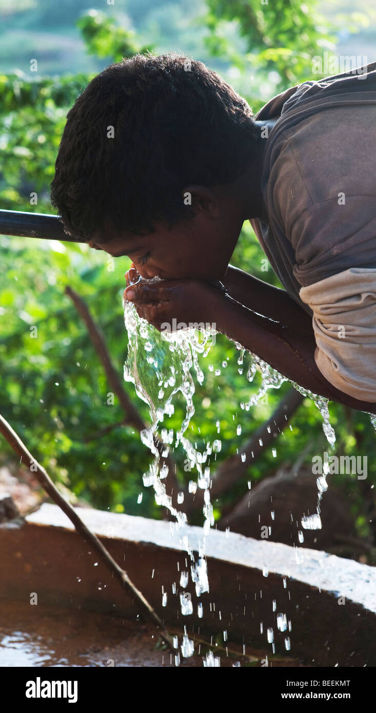 Young Indian boy drinking from a water tap. India - Stock Image