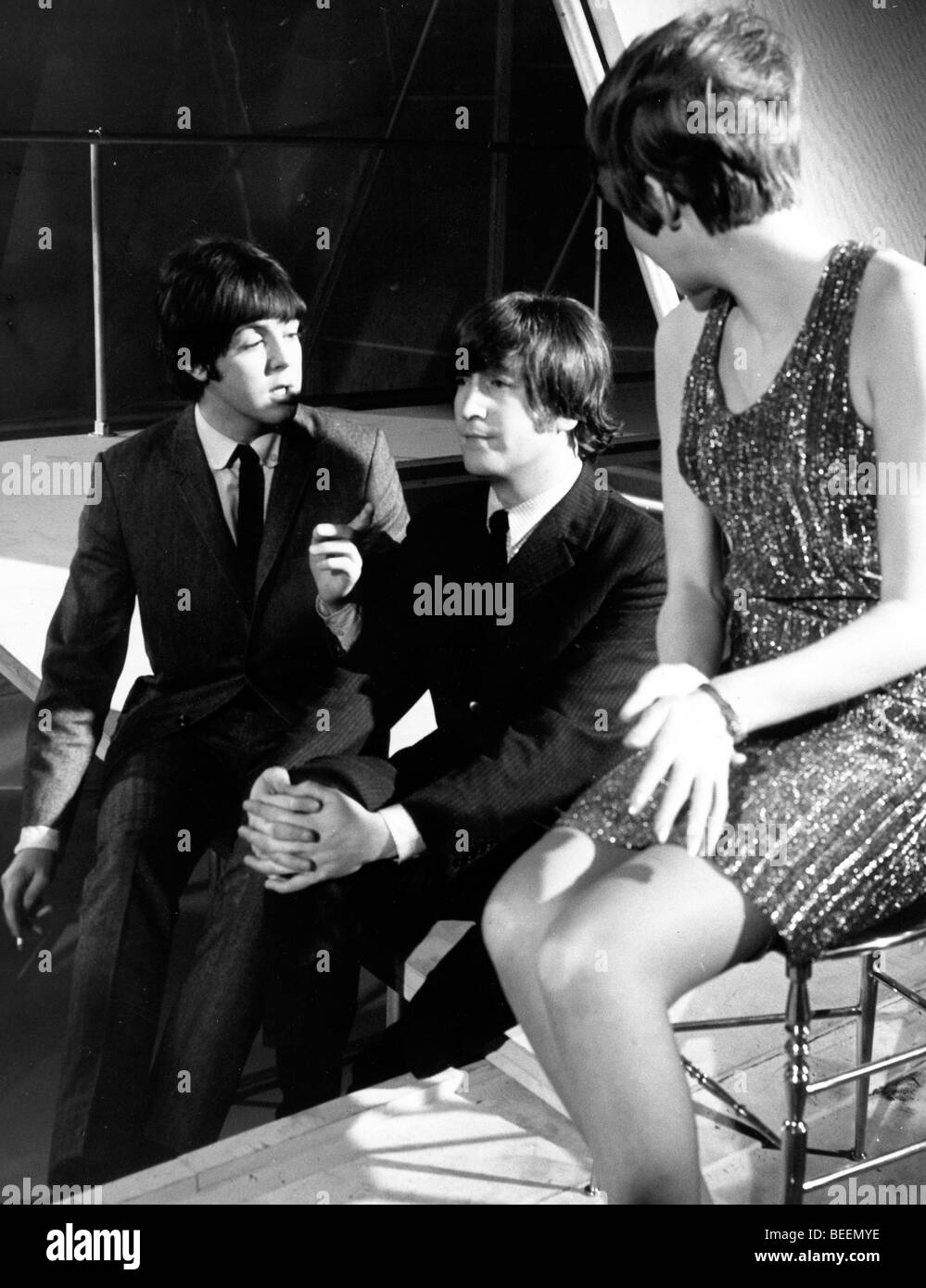 The Beatles with Cilla Black taking a break from filming a TV special Stock Photo