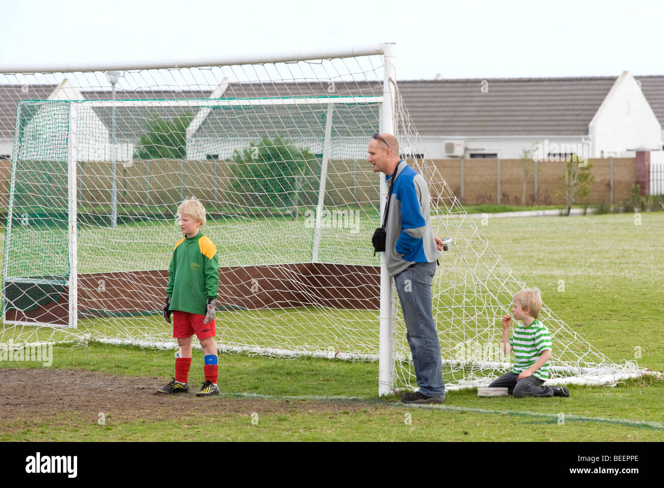 Under 11 goal keeper and his father during a soccer match, Cape Town, South Africa - Stock Image