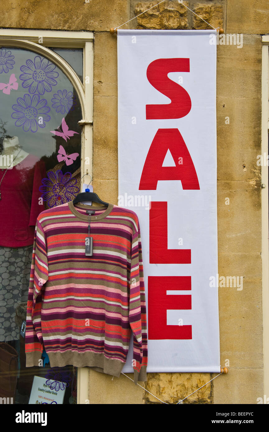Clothing shop sales in Cotswold village of Bourton on the Water Gloucestershire England UK - Stock Image
