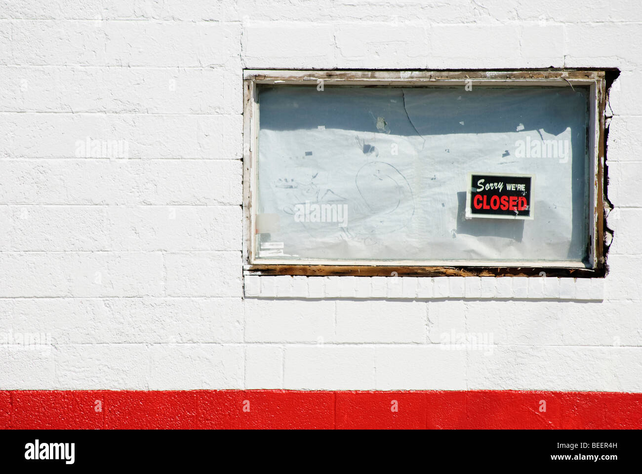 boarded up white window of bankrupt business with 'Sorry we're closed' sign - Stock Image