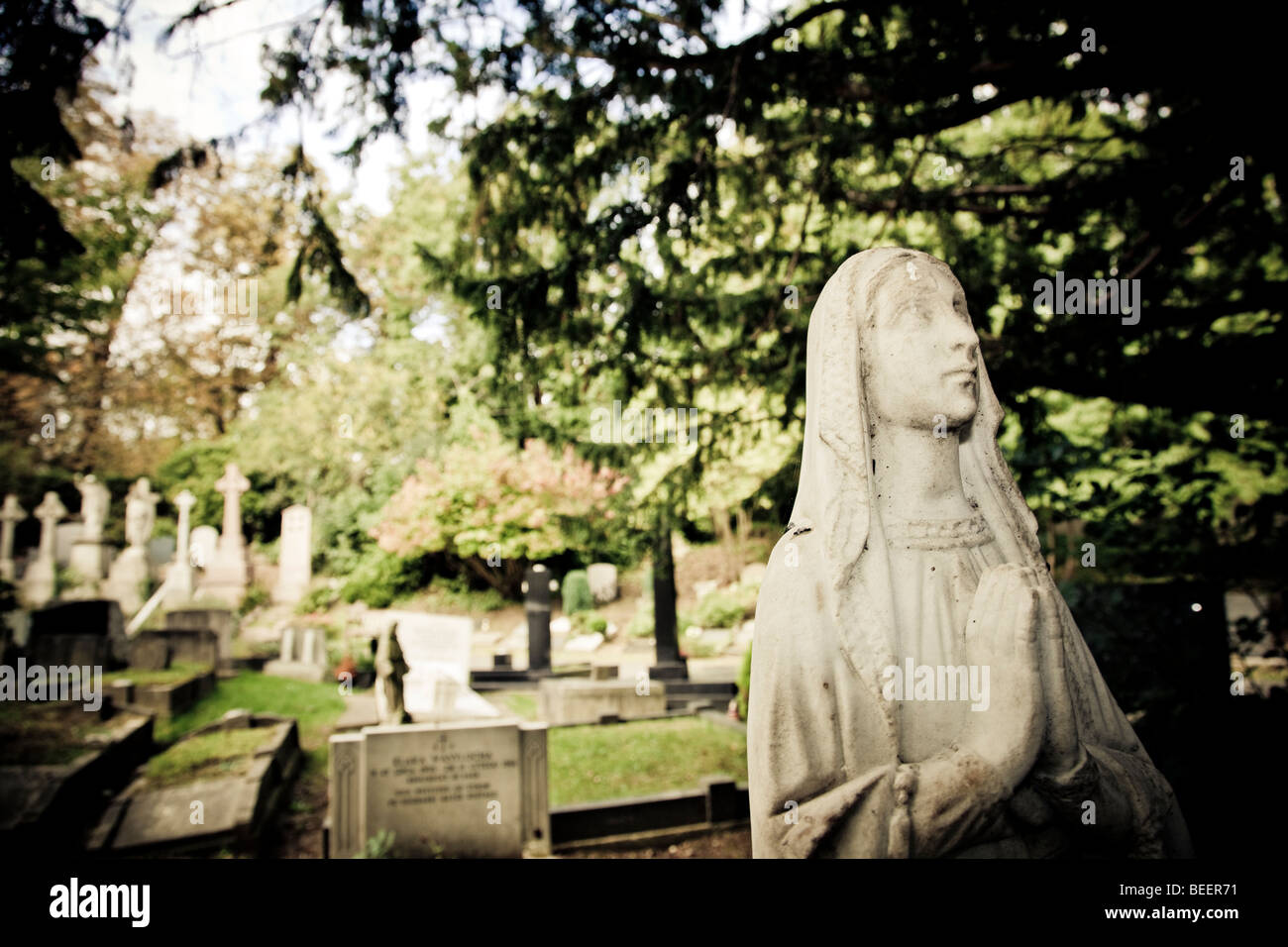 A praying female figure with a shawl made of stone stands over a grave amongst trees in Highgate Cemetery London - Stock Image