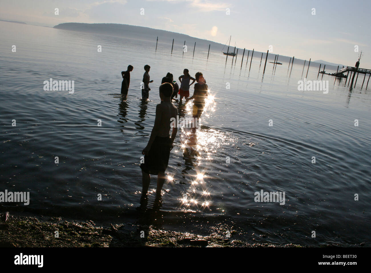 Kids on summer vacation wade into the water at sunset, Washington State, USA - Stock Image