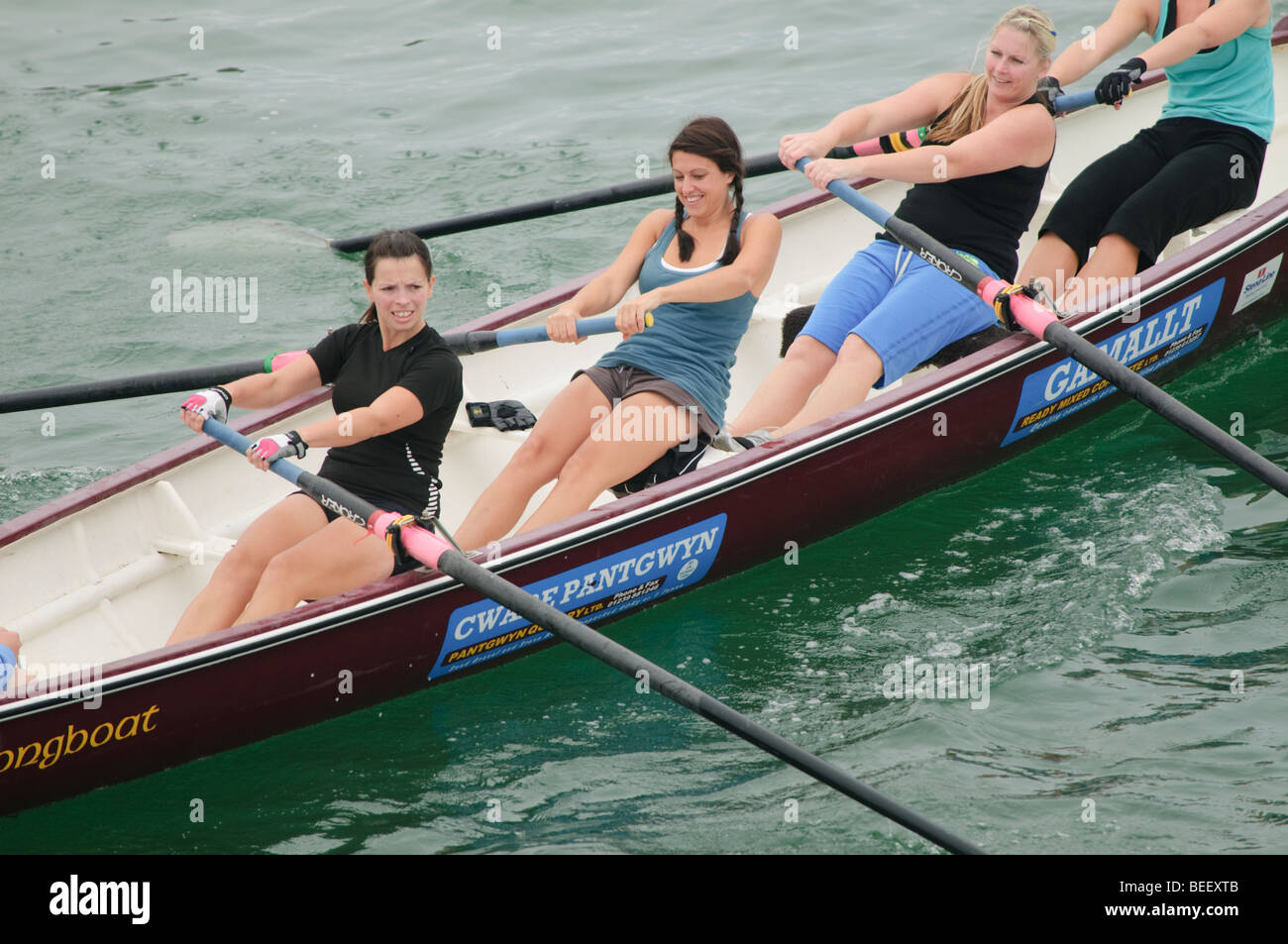 Four women rowing celtic longboat in a competitive race at Aberystwyth Wales UK - Stock Image