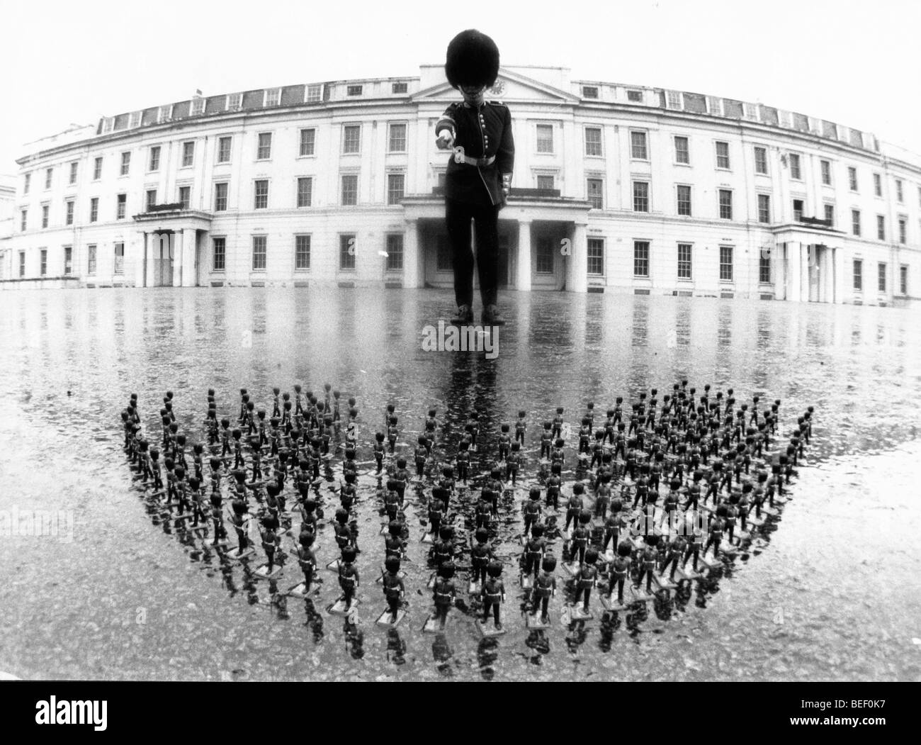 A guard and tiny toy soldiers. Stock Photo
