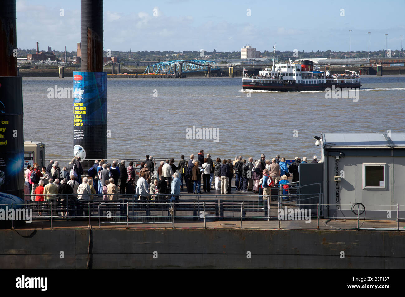 tourists and commuters queue up at the pier head floating ferry terminal waiting for the mersey ferry on the river - Stock Image