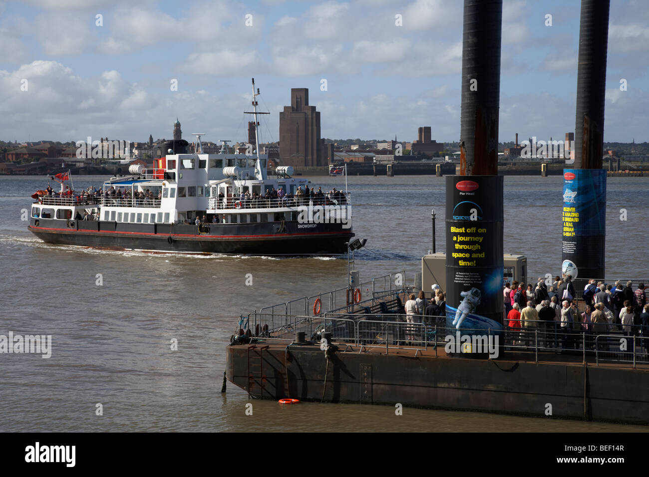 tourists and commuters queue up at the pier head floating ferry terminal for the mersey ferry on the river mersey - Stock Image