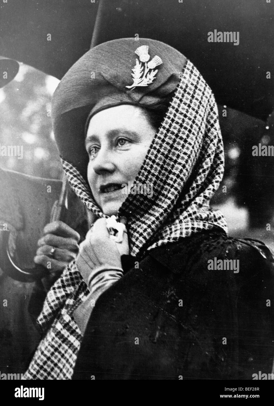 Elizabeth Bowes-Lyon, the queen consort, puts a scarf over her hat against the heavy rain. Stock Photo
