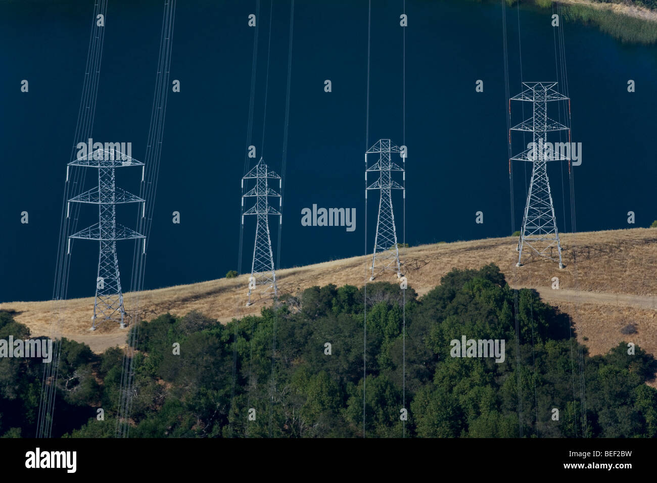 aerial view above power transmission lines towers at California reservoir Stock Photo