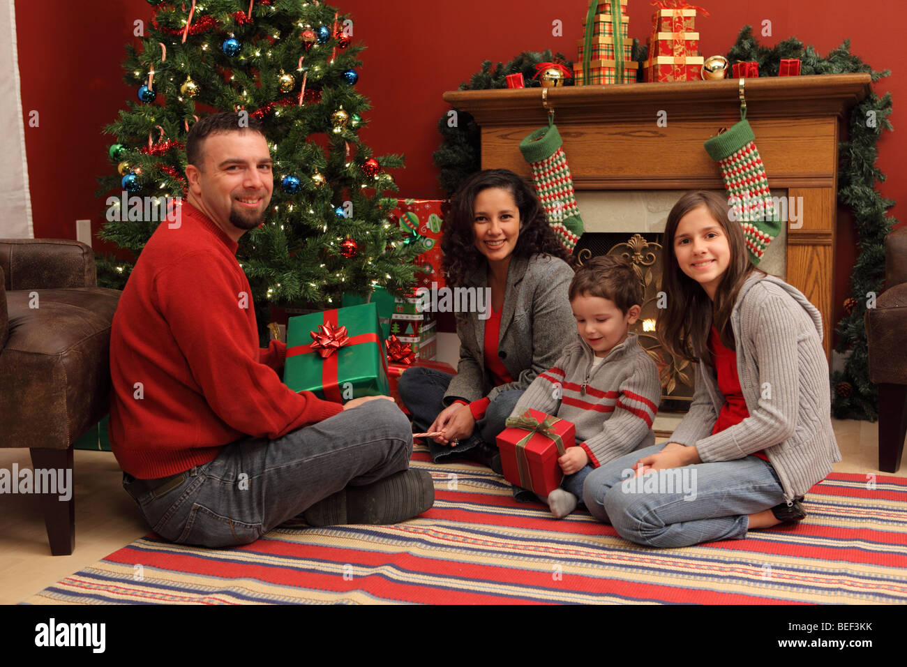 Family with gifts by Christmas tree - Stock Image