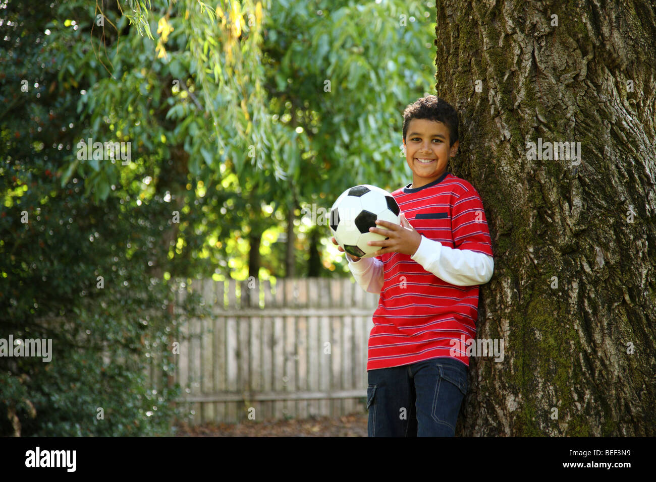 Portrait of boy outdoors with soccer ball - Stock Image