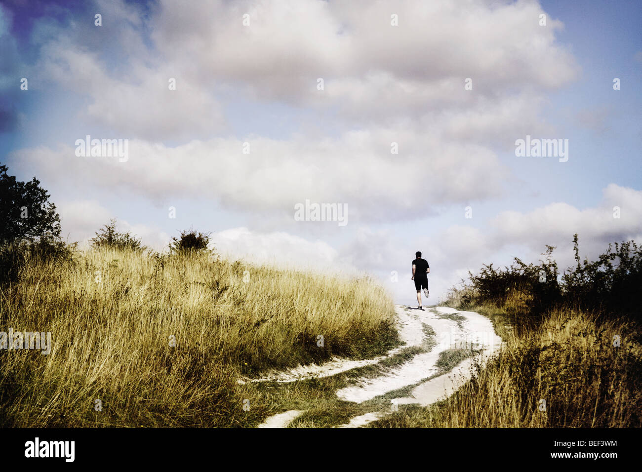 man running on a pathway through fields - Stock Image