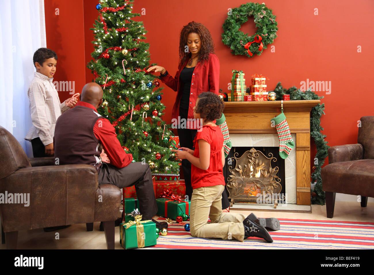 Family decorating Christmas tree - Stock Image