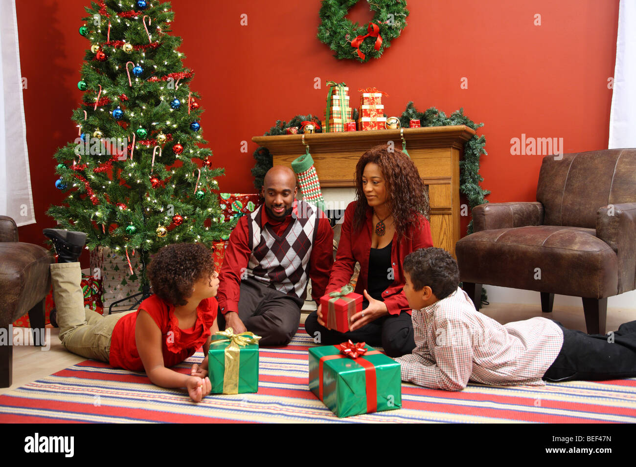 African American family by Christmas tree - Stock Image