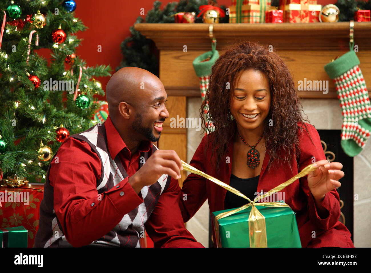 Couple opening present together by Christmas tree - Stock Image