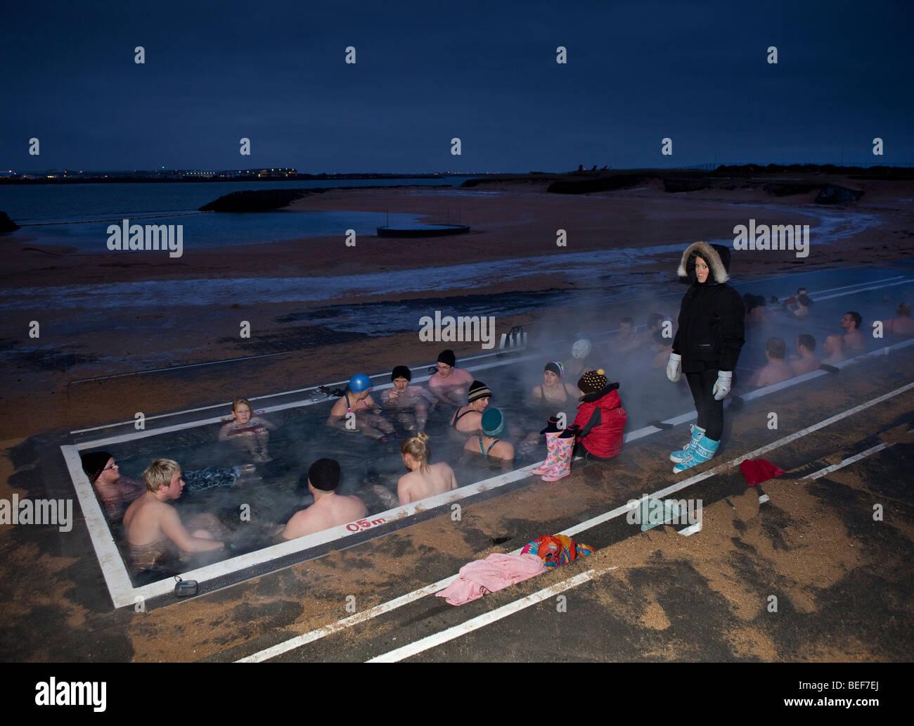 Group in Geothermal heated hot tub, winter evening, Reykjavik ...