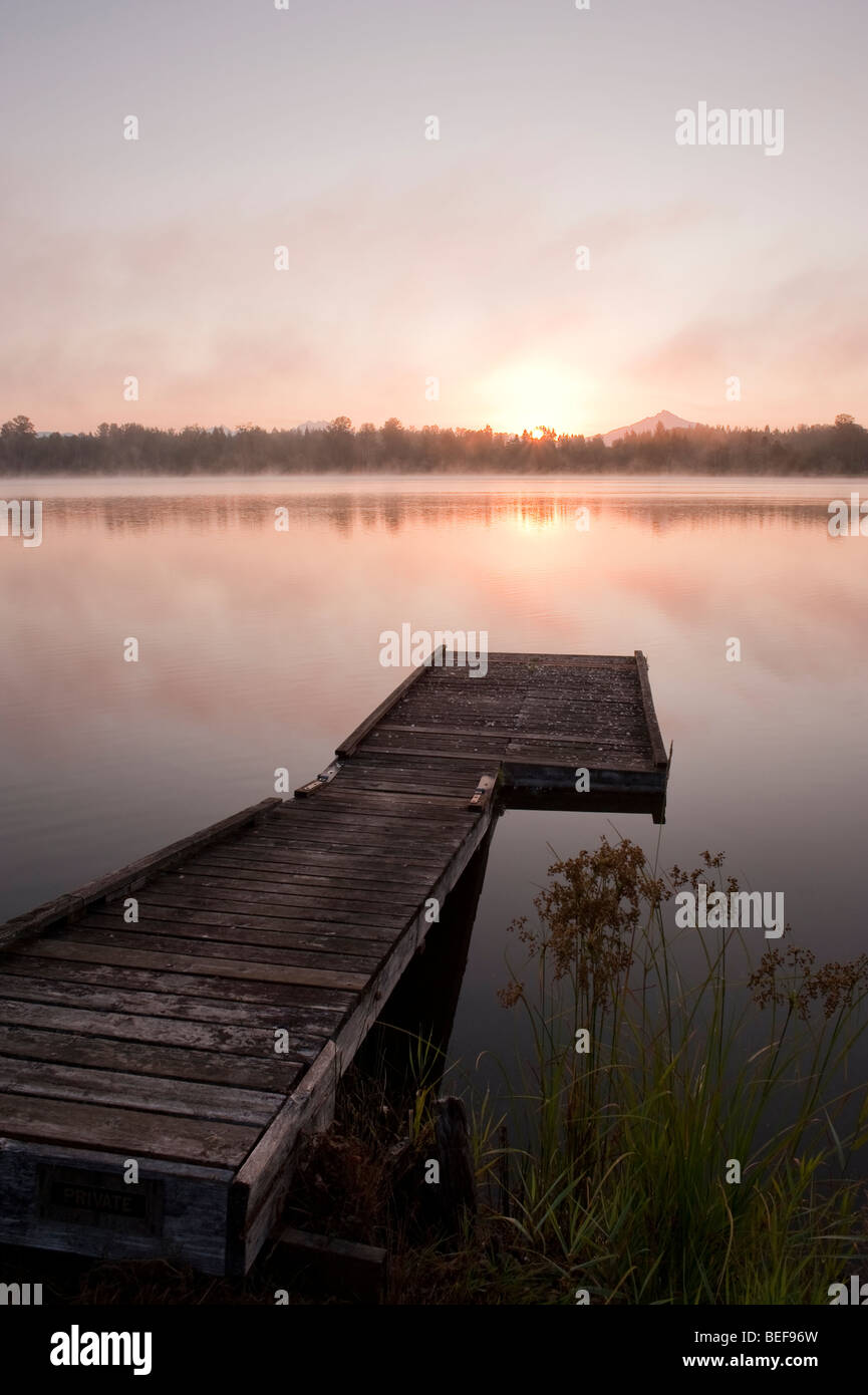 Sunrise at Lake Cassidy in fog with Mount Pilchuck and dock in foreground - Stock Image