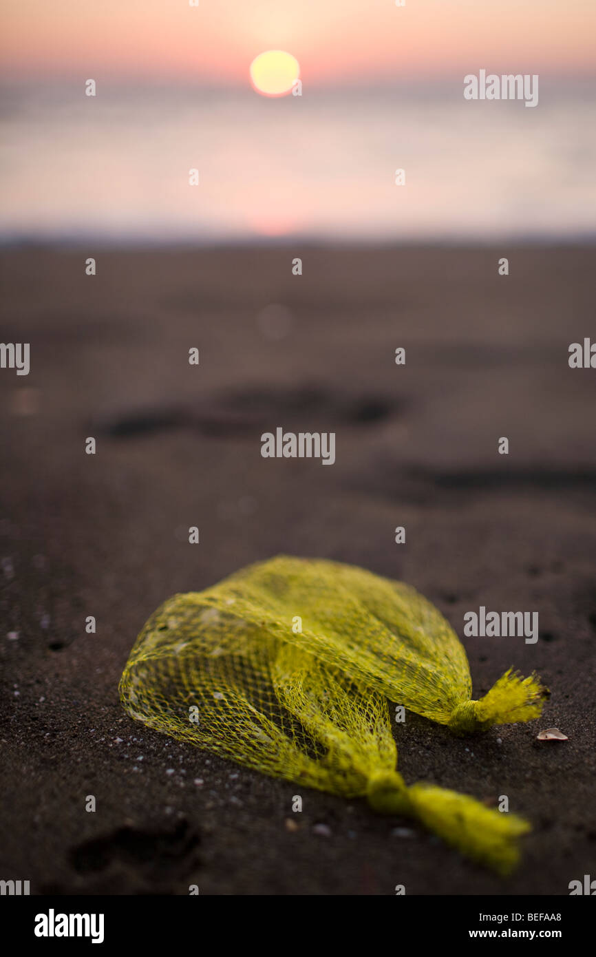 Sun setting over the ocean with trash laying on the beach in Playas del Coco, Guanacaste, Costa Rica. Stock Photo