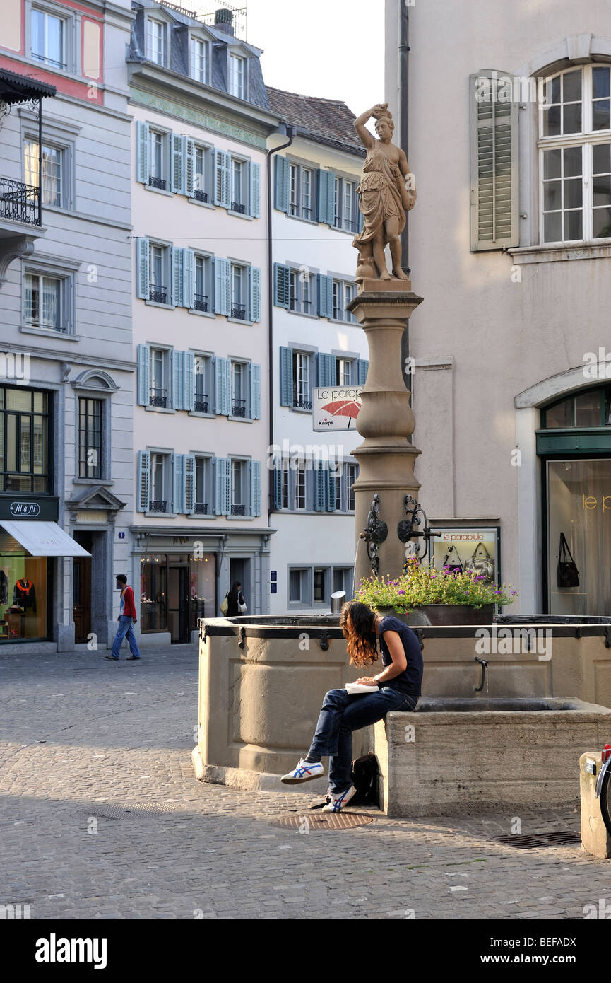 Woman reading by a fountain in a street which is part the old town of Zurich, Switzerland - Stock Image