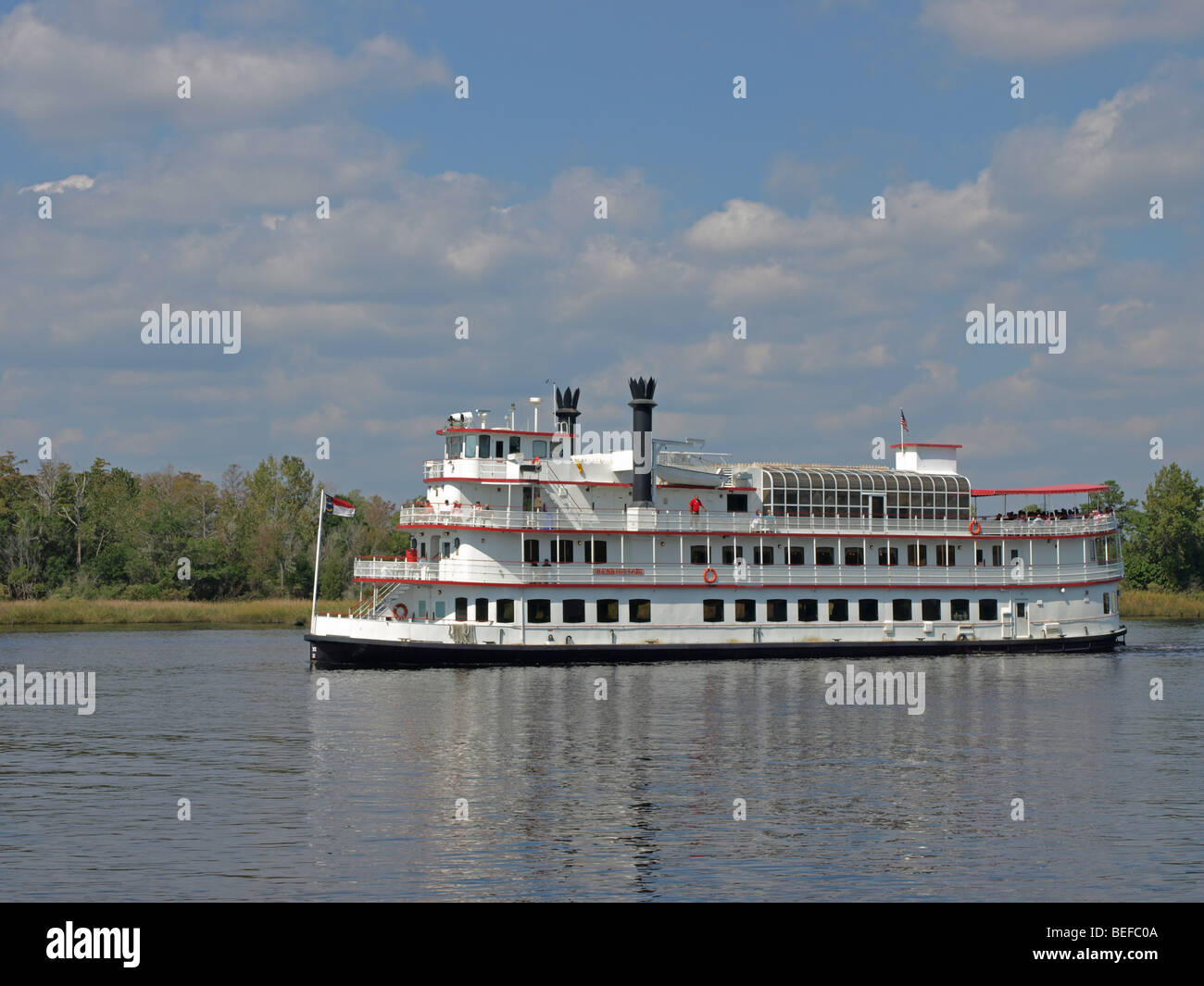 replica paddle-wheel riverboat boat on river with cloudy sky behind, large three deck white ship with smokestacks Stock Photo
