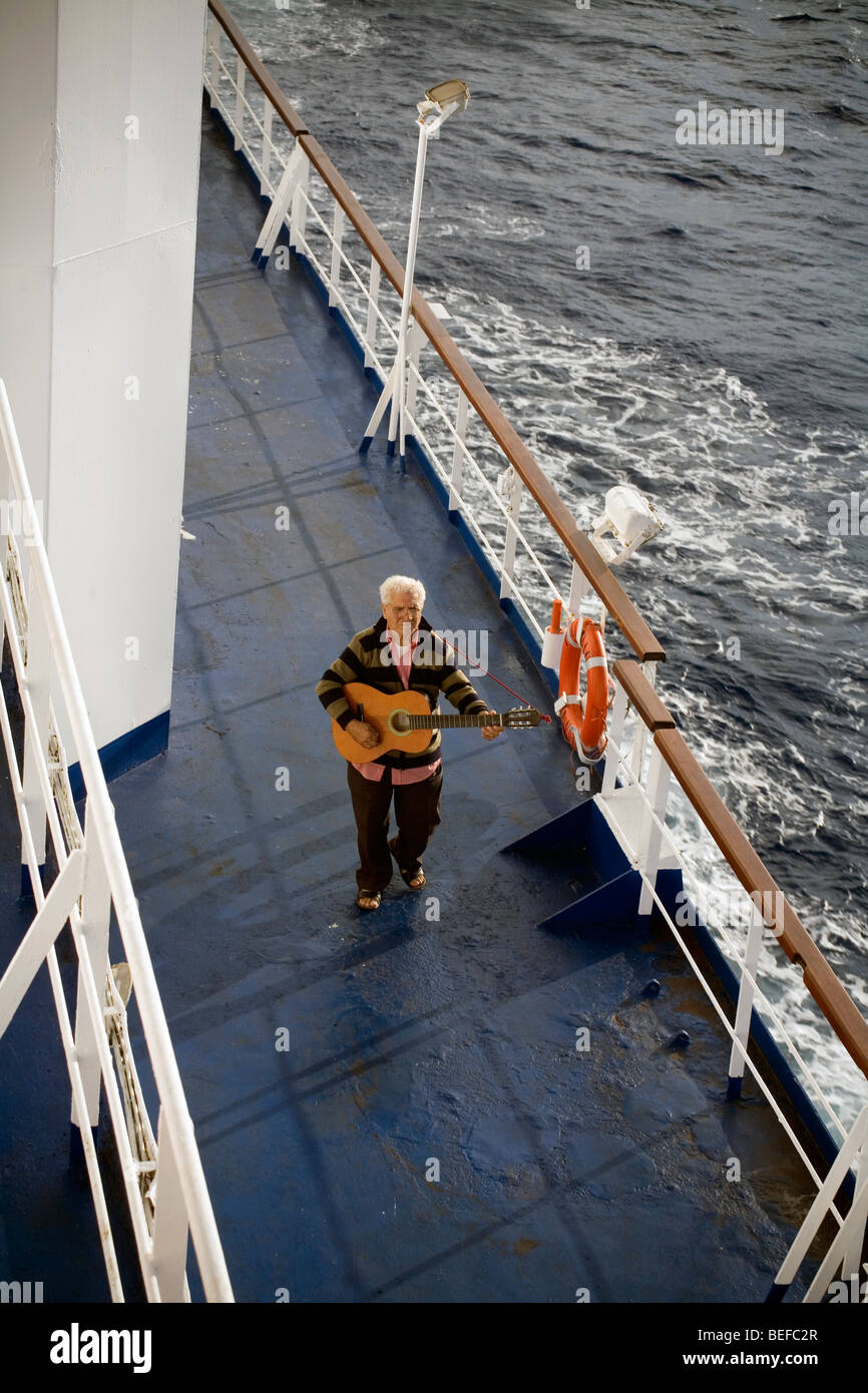Man walking around and playing guitar on the deck of a ferry - Stock Image