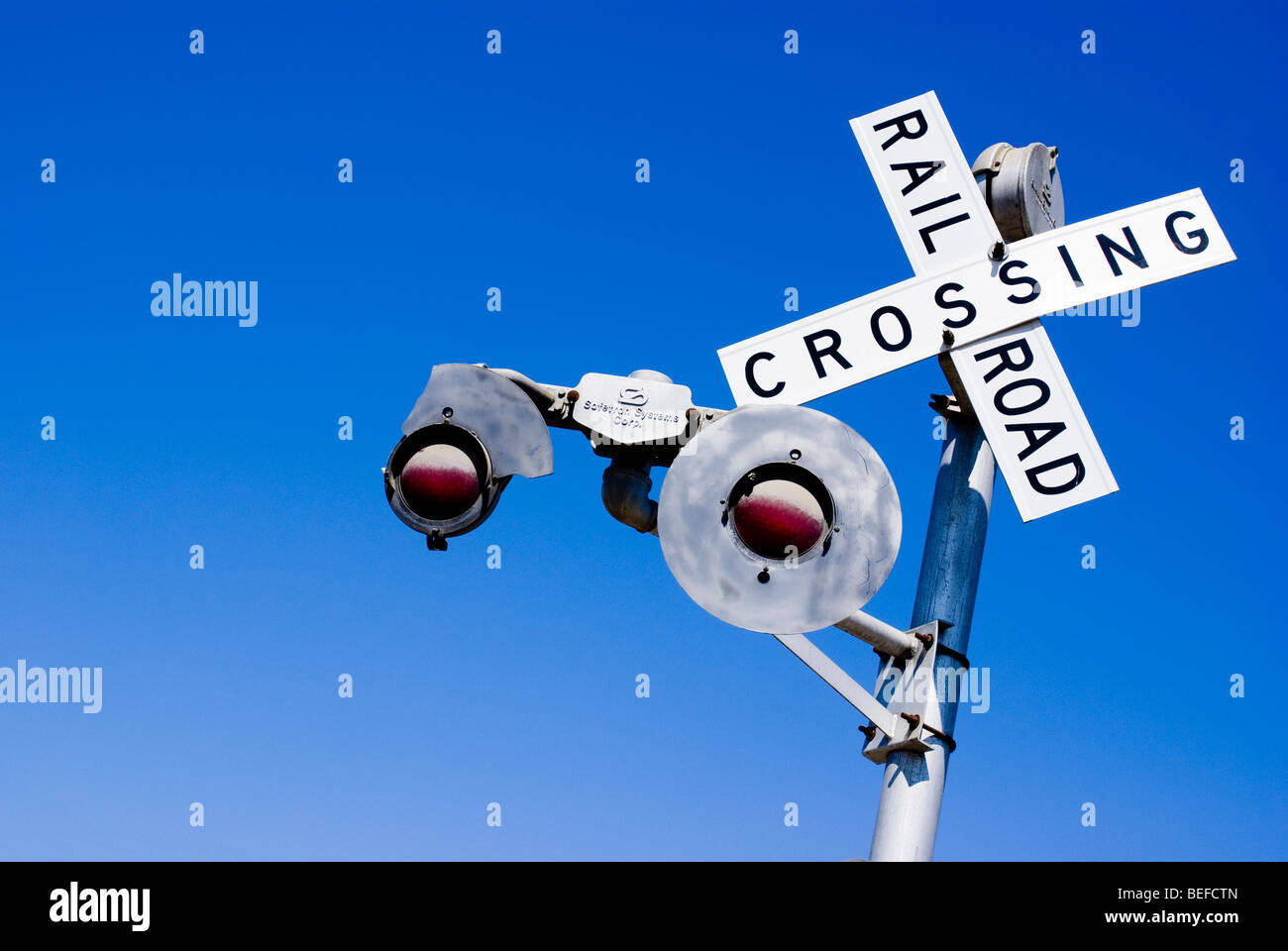 A railroad crossing sign against a blue sky. - Stock Image