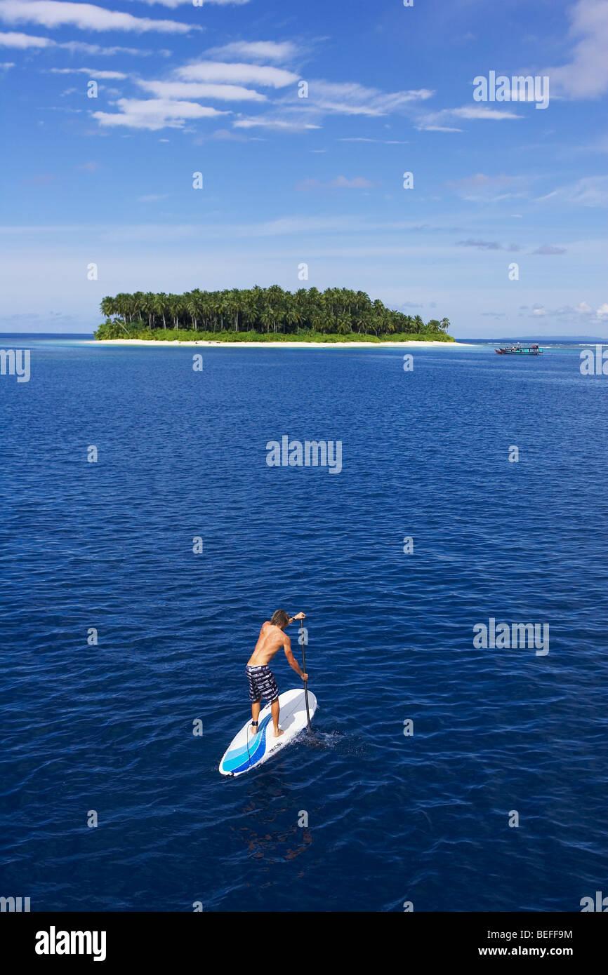 Paddle boarding to deserted island - Stock Image
