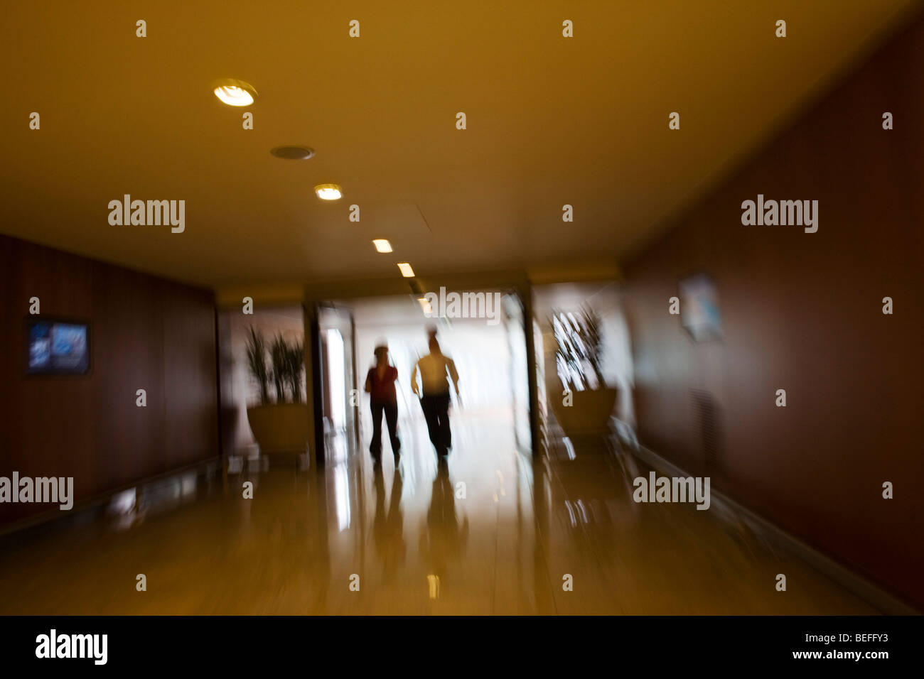 Two hotel guests head for exit in connecting corridor in Sofitel at Heathrow's terminal 5 hotel. - Stock Image