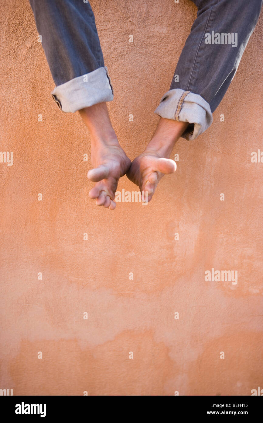 man dangling his feet against an adobe wall - Stock Image
