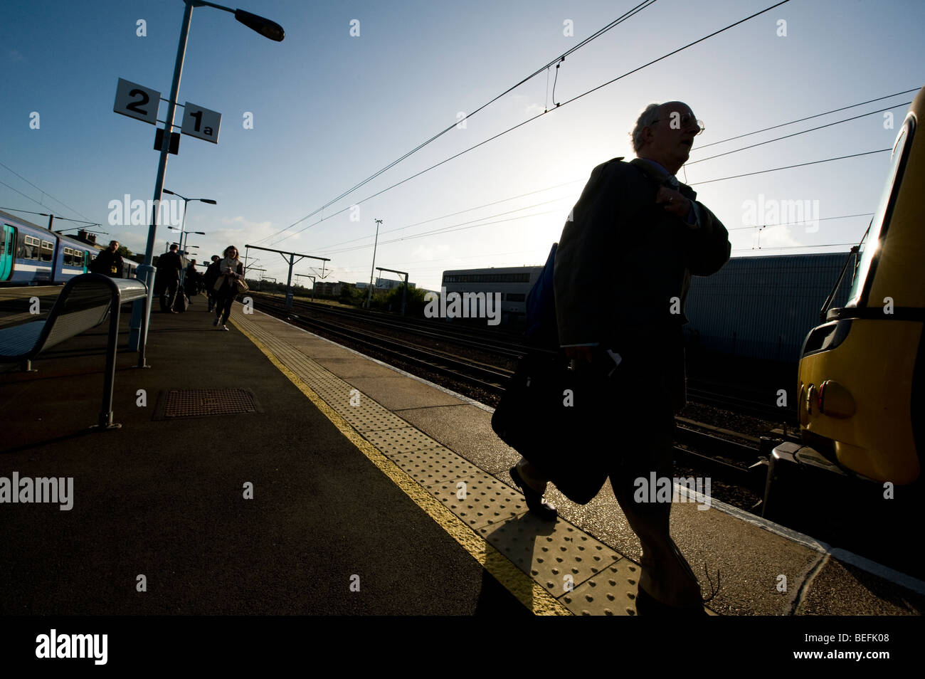 Silhouette of passengers walking along a railway station platform in England. - Stock Image