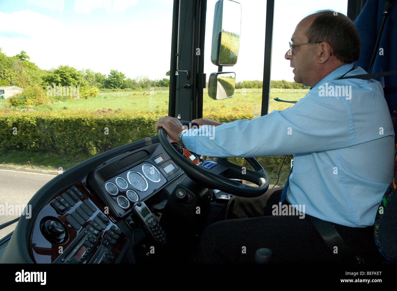 Passenger view of coach driver and road ahead - Stock Image