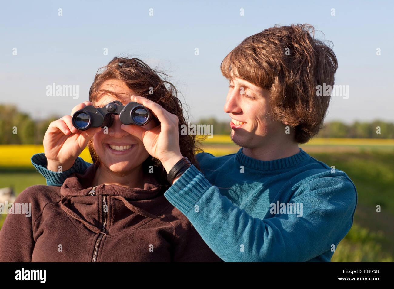 Couple using binoculars . - Stock Image