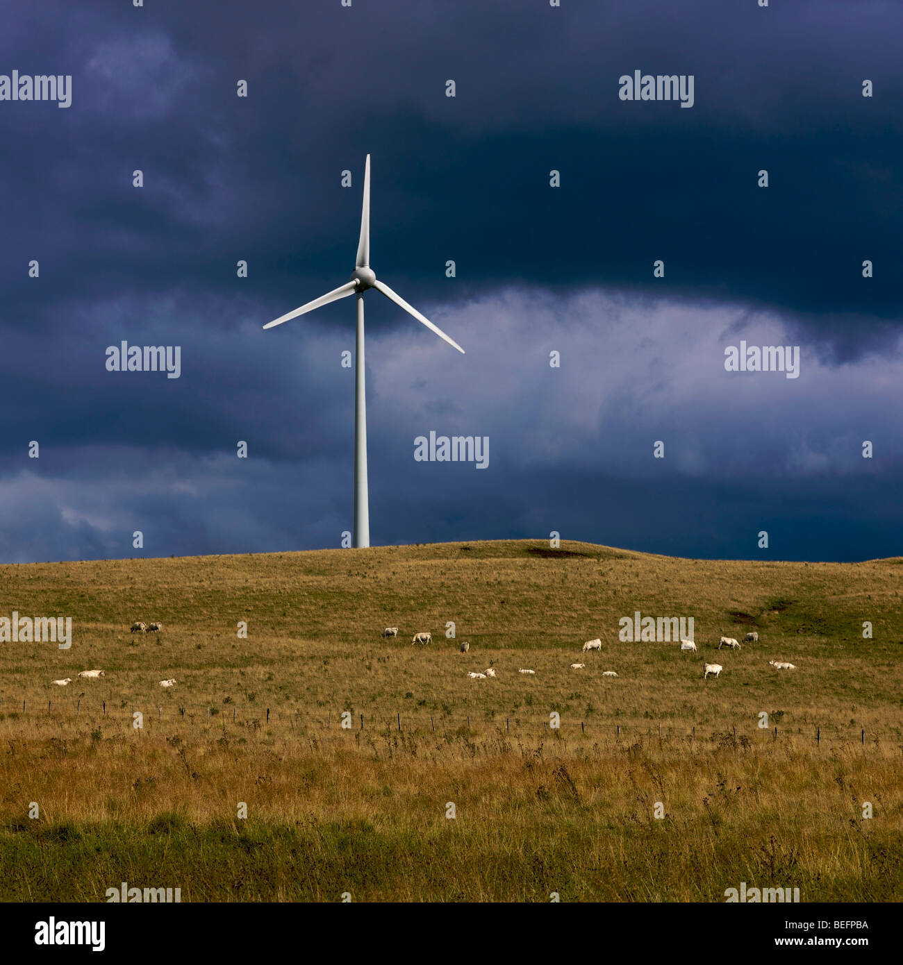 Large wind turbine on a plateau in a rural setting with a dark stormy sky - Stock Image